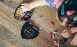 Baby, das mit den Haarspangen sitzen im Boden spielt lizenzfreie stockbilder