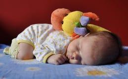Baby, das mit einem Plüschspielzeug schläft lizenzfreies stockfoto