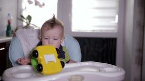 Baby, das mit einem Spielzeugauto, sitzend in einem Babystuhl spielt Ein Einjahresschätzchen stock video