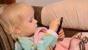 Baby, das mit einem Telefon spielt stock footage