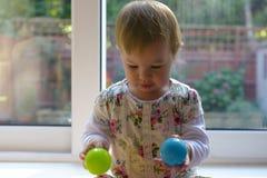 Baby, das mit farbigen Bällen spielt stockfotografie