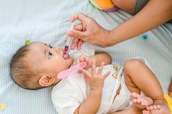 Baby, das mit flüssiger Medizin, Gesundheitswesenkonzept einzieht Stockbild
