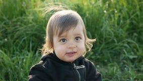 Baby, das mit Löwenzahn auf einem grünen Gebiet im Sommer steht stock video footage