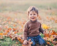 Baby, das mit Laub im Herbstpark spielt stockbilder