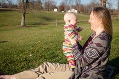 Baby, das mit Mutter draußen lacht lizenzfreie stockfotografie