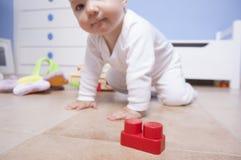 Baby, das mit Plastikbausteinen spielt Lizenzfreie Stockfotos