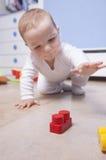 Baby, das mit Plastikbausteinen spielt Lizenzfreies Stockbild