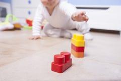 Baby, das mit Plastikbausteinen spielt Lizenzfreie Stockbilder