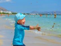 Baby, das mit Sand auf dem Strand von Mallorca spielt Lizenzfreie Stockfotografie