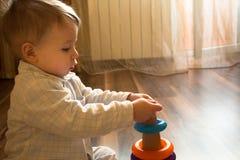 Baby, das mit Spielwaren im Pyjama spielt Stockfotografie