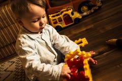 Baby, das mit Spielwaren im Pyjama spielt Stockfoto