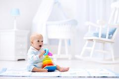 Baby, das mit Spielzeugpyramide spielt Kinderspiel Lizenzfreies Stockbild