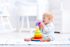 Baby, das mit Spielzeugpyramide spielt Kinderspiel Lizenzfreie Stockbilder