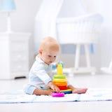 Baby, das mit Spielzeugpyramide spielt Kinderspiel Stockfotos
