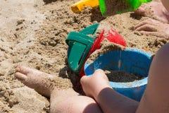 Baby, das mit Strandeimer und -schaufel spielt stockfotos