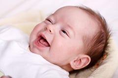Baby, das mit zahnlos Lächeln lacht Stockbild
