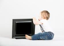 Baby, das nahe bei Bilderrahmen sitzt und hinten schaut Stockfotografie