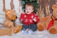 Baby, das nahe bei zwei Teddybären sitzt Stockbild