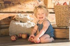 Baby, das nahe hölzerner Scheune sitzt und lächelt Stockbilder