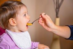 Baby, das Püree von einem Löffel in der Hand von isst stockbilder