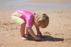 Baby, das am Sandstrand sich duckt Lizenzfreie Stockfotos
