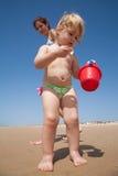 Baby, das Seeoberteile im roten Eimer sammelt Lizenzfreie Stockfotos