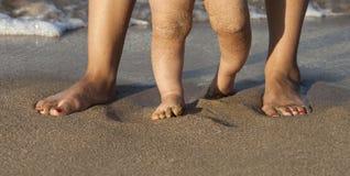 Baby, das seine ersten Schritte auf dem Strand tut Stockfotos