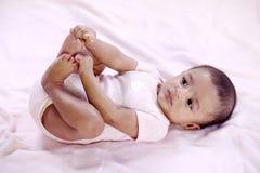 Baby, das seine Zehen hält lizenzfreie stockbilder