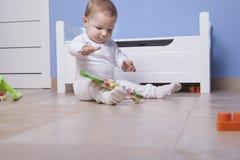 Baby, das in seinem Spielzeugraum spielt Stockfotografie
