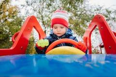 Baby, das am Steuer von einem children& x27 sitzt; s-Auto auf dem Spielplatz stockbild