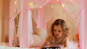 Baby, das Tablette im Schlafzimmer verwendet Kind, das ein Video auf einem Bildschirm aufpasst und in ihrem Raum spielt stock footage