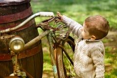 Baby, das um das alte Fahrrad geht Lizenzfreies Stockfoto
