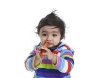 Baby, das versucht, Karotte zu essen Stockfoto