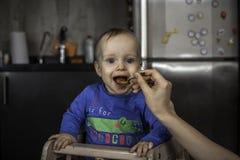 Baby, das von der Mutter in der Küche eingezogen wird Lizenzfreie Stockfotos