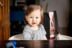 Baby, das von ihrem Hochstuhl schaut Lizenzfreies Stockbild