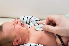 Baby, das während Sie durch Doktor schreit, überprüft werden Stockfoto