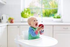 Baby, das zu Hause Apfel in der weißen Küche isst Lizenzfreies Stockfoto