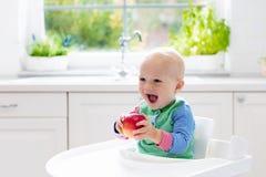 Baby, das zu Hause Apfel in der weißen Küche isst Stockfoto