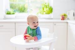 Baby, das zu Hause Apfel in der weißen Küche isst Stockfotografie