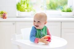 Baby, das zu Hause Apfel in der weißen Küche isst Stockbilder