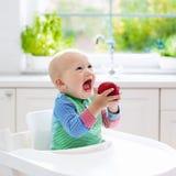 Baby, das zu Hause Apfel in der weißen Küche isst Lizenzfreie Stockfotografie