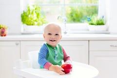 Baby, das zu Hause Apfel in der weißen Küche isst Stockbild