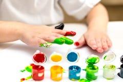 Baby, das zu Hause mit bunten Farben spielt Lizenzfreies Stockfoto