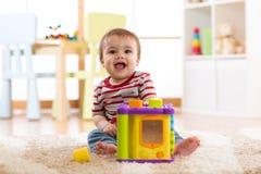 Baby, das zu Hause mit bunten Spielwaren spielt Glückliche sieben Monate alte Säuglingskinderspielen und -entdeckung Lizenzfreie Stockfotos