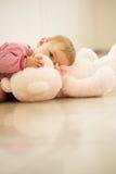 Baby, das zu Hause rosafarbenen Teddybären streichelt Stockfotografie