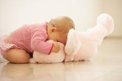 Baby, das zu Hause rosafarbenen Teddybären streichelt Stockbilder