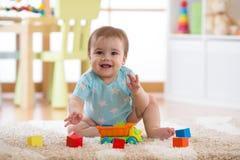 Baby, das zu Hause Spielwaren oder Kindergarten spielt lizenzfreie stockfotografie