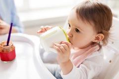 Baby, das zu Hause von der Tüllenschale im Highchair trinkt Stockfotos