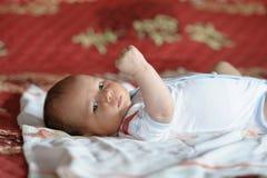 Baby, das zurück auf seinem auf dem Bett liegt lizenzfreies stockfoto