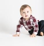 Baby, das zur Seite im Flanell und in Jeans schauen neugierig sitzt lizenzfreies stockfoto